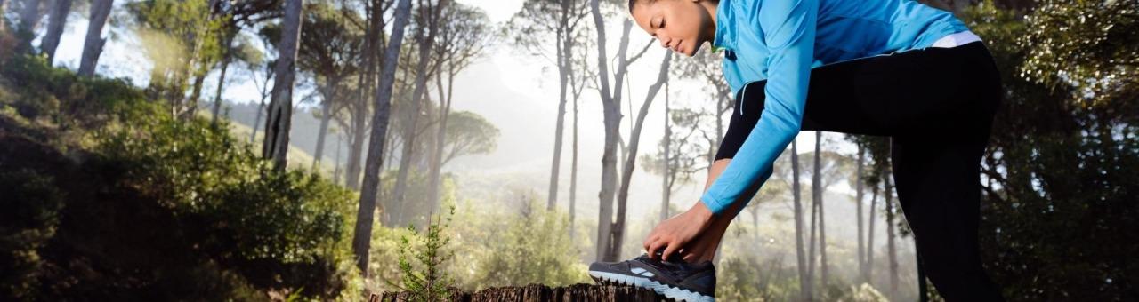 meisje strikt haar veters in het bos